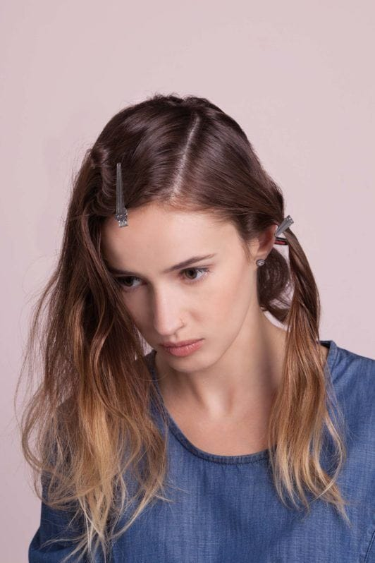woman with ombre hair creates flapper hairstyles and adds clip