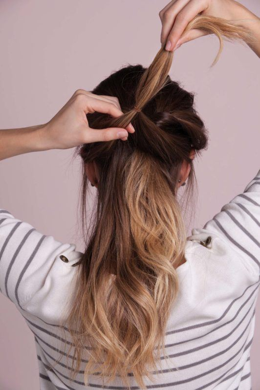 woman with ombre hair creates french braid and secures second ponytail