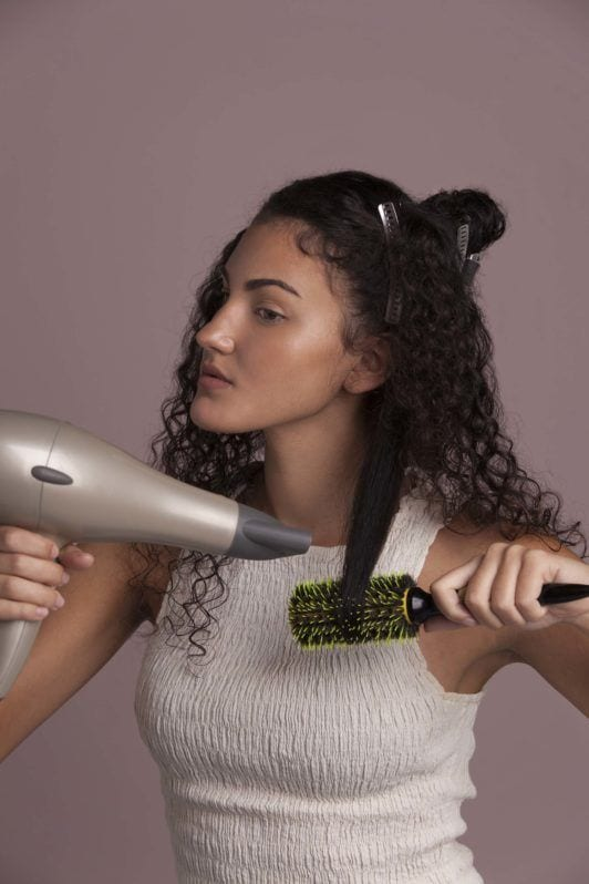 brunette woman shows how to blow-dry hair with round brush