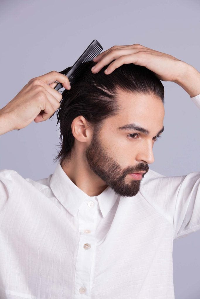 brunette man shows how to style your hair and combs hair