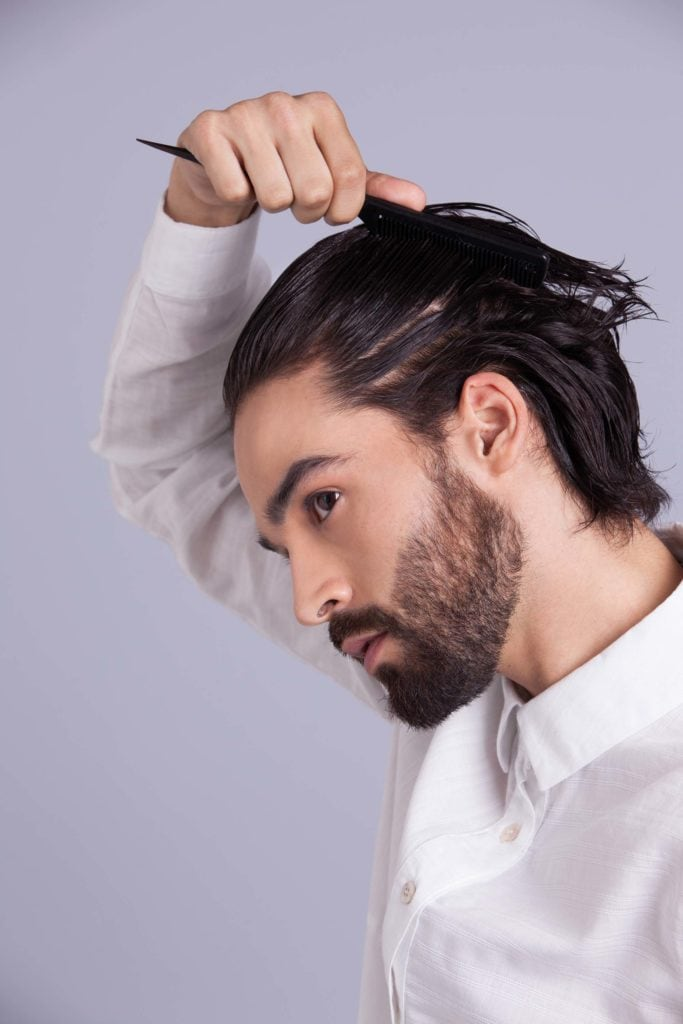 brunette man shows how to style your hair and creates shape