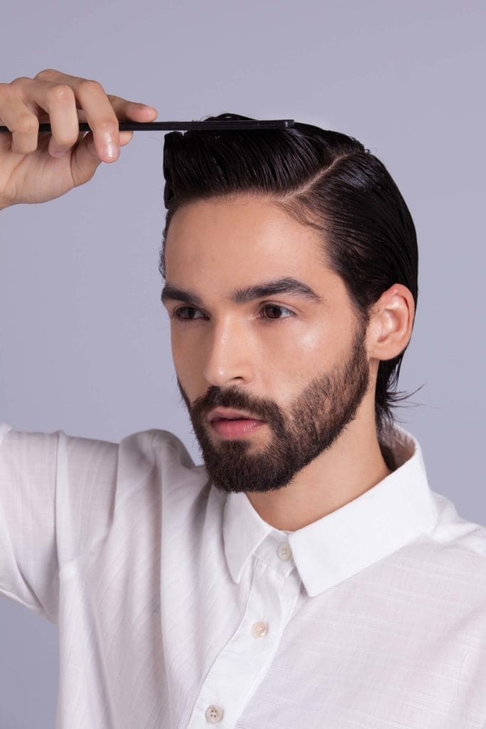 brunette man shows how to style your hair and creates volume