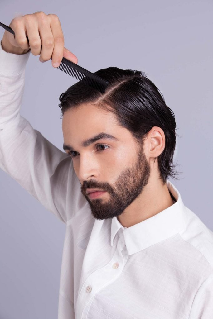 brunette man shows how to style your hair and creates part