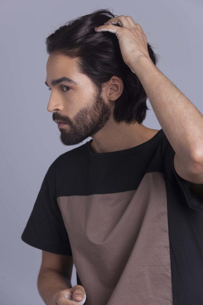 brunette man creates man braid and applies product