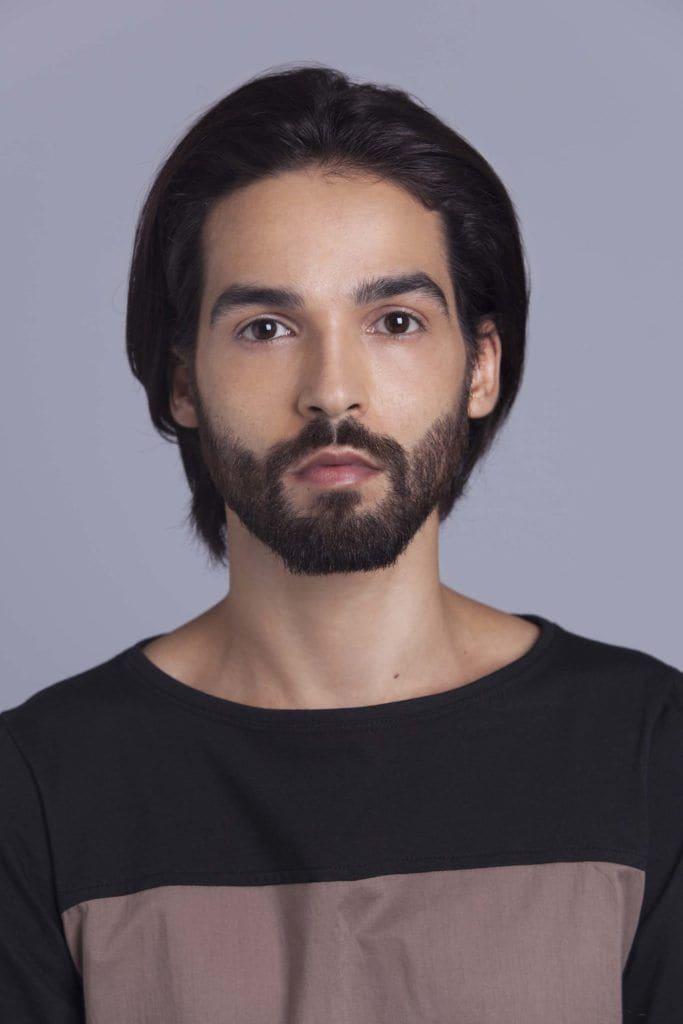 brunette man creates man braid on clean hair