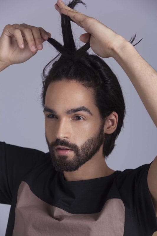 brunette man creates man braid and divides and braids