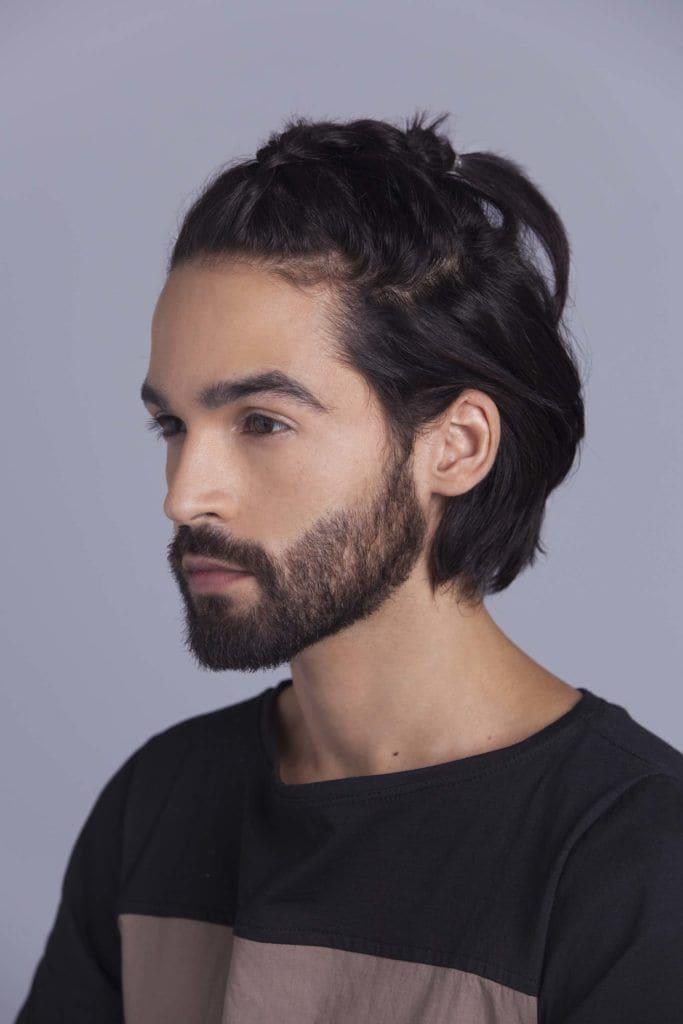 brunette man creates man braid and secures