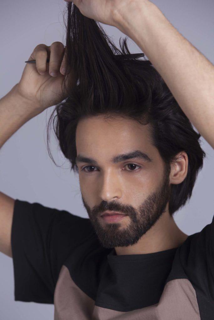 brunette man creates man braid and combs through