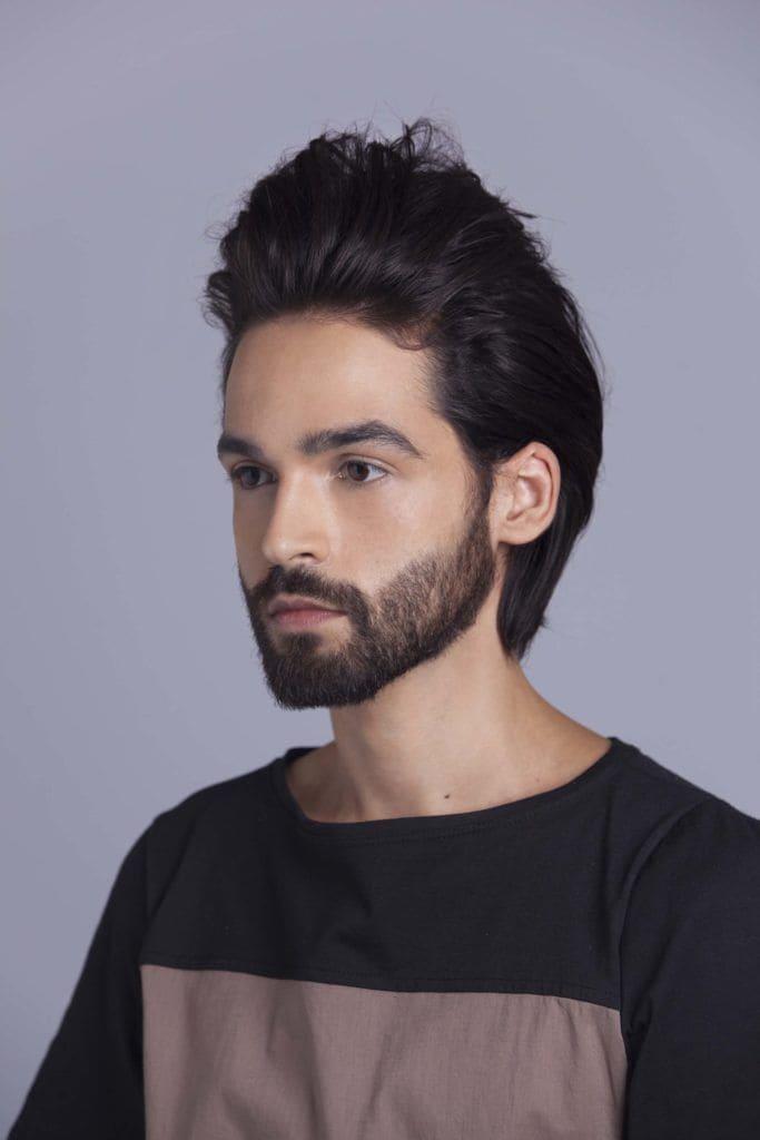 brunette man creates man braid and molds shape