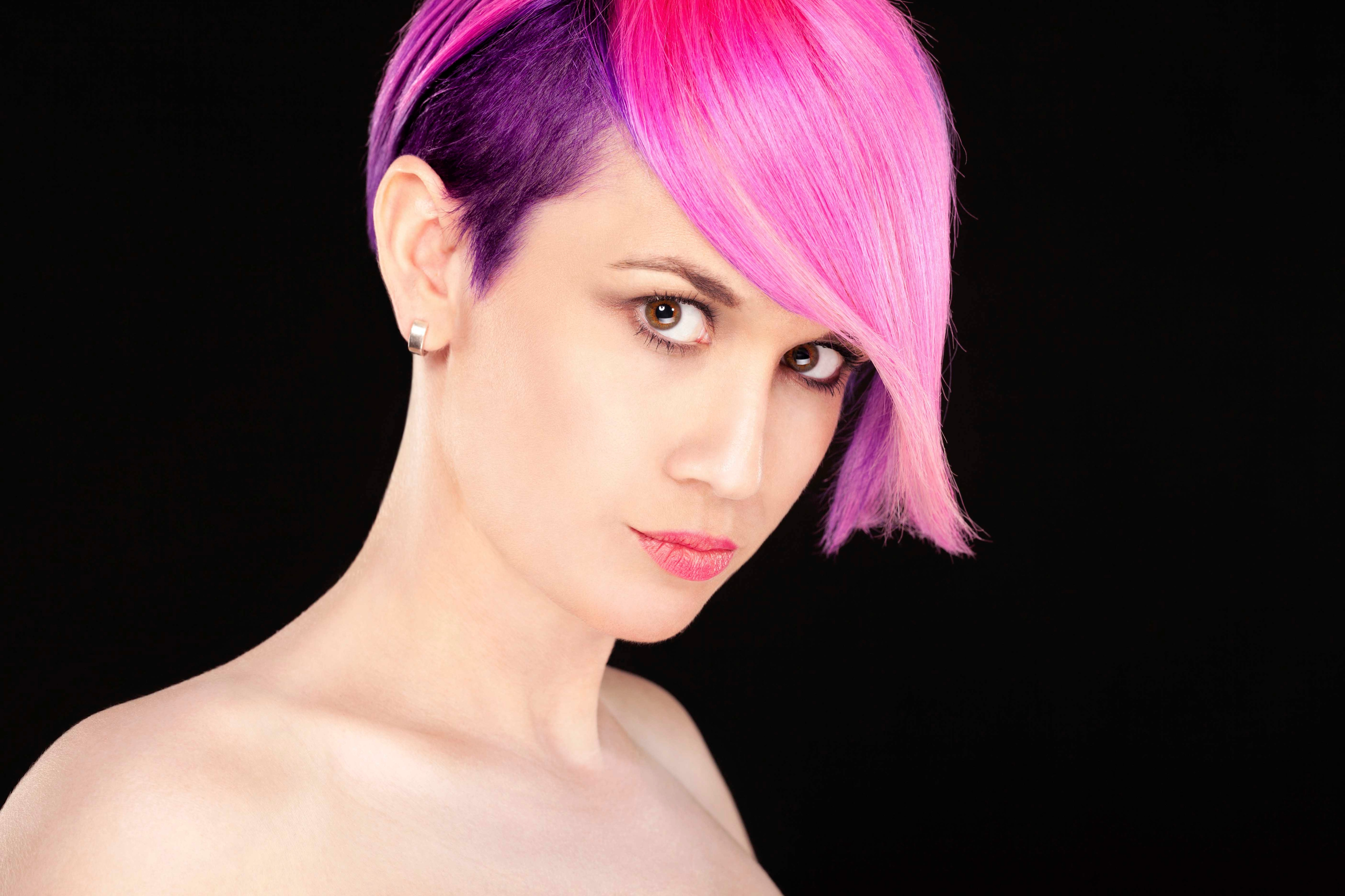 woman with pink hair wearing one of the stylish half shaved hairstyles.