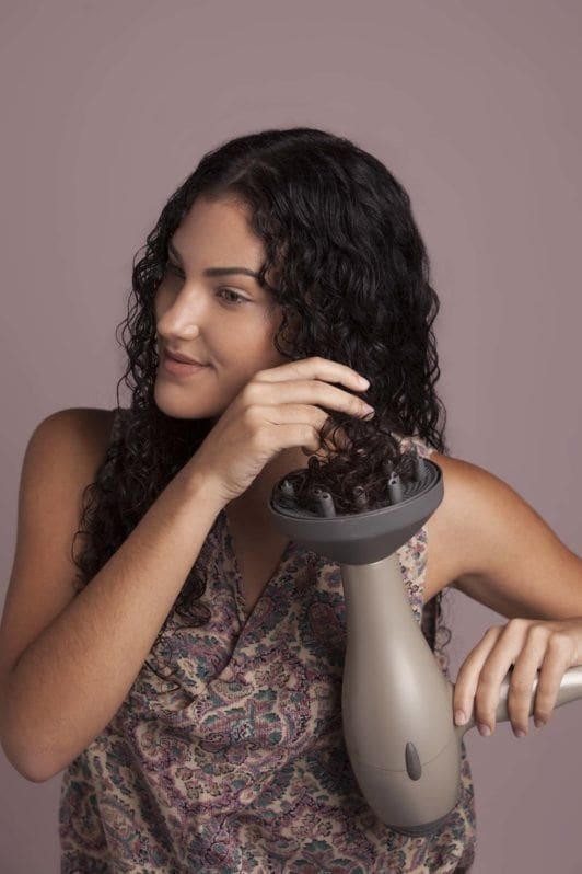 brunette woman uses hair dryer diffuser and dries hair