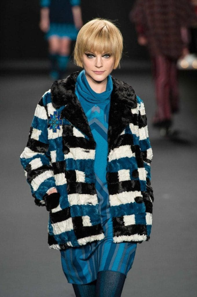 a woman with short haircut wearing blue coat walking on a catwalk