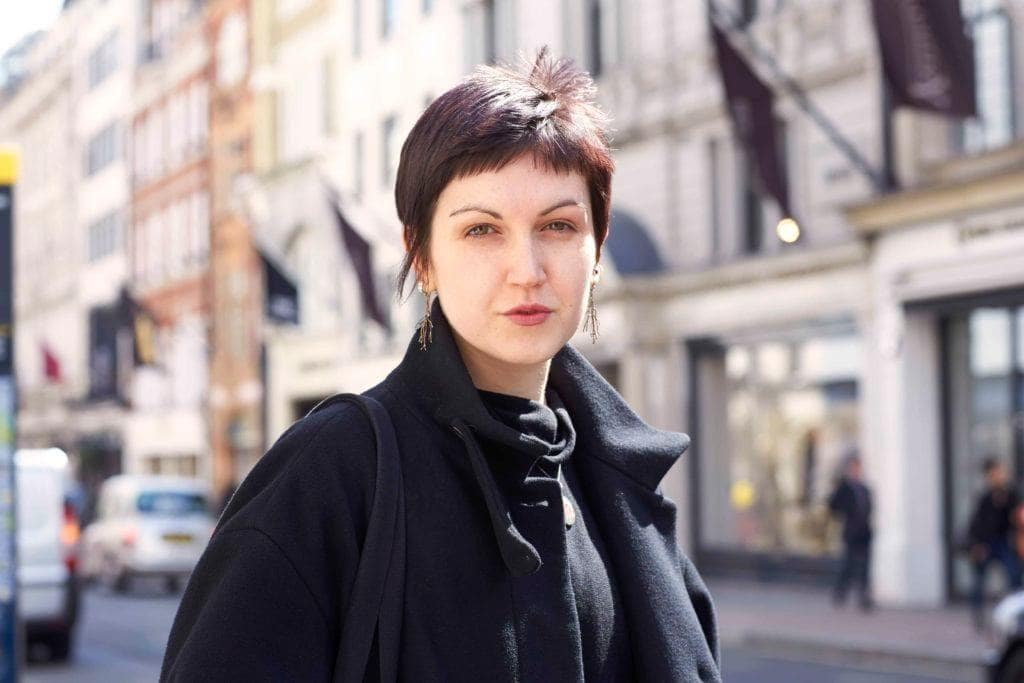 a woman with short haircut walking in a city on the street wearing blact coat and scarf