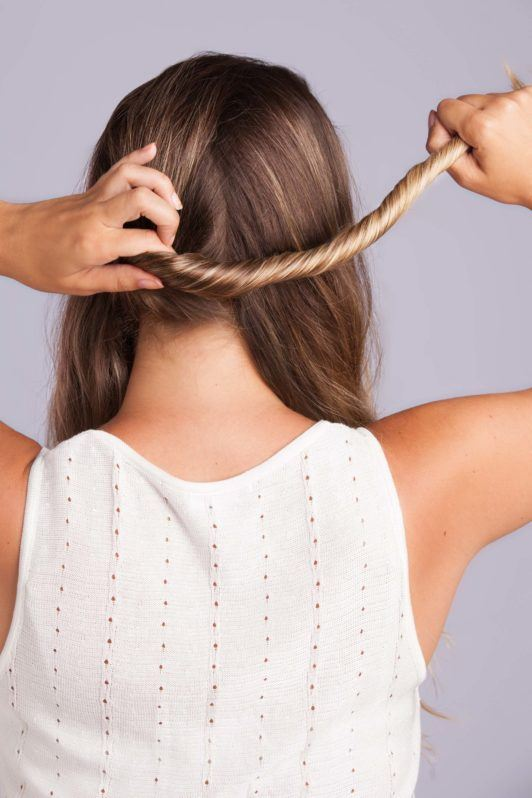 Wedding Hair Buns - Step 3 - woman with bronde hair twisting on section of hair