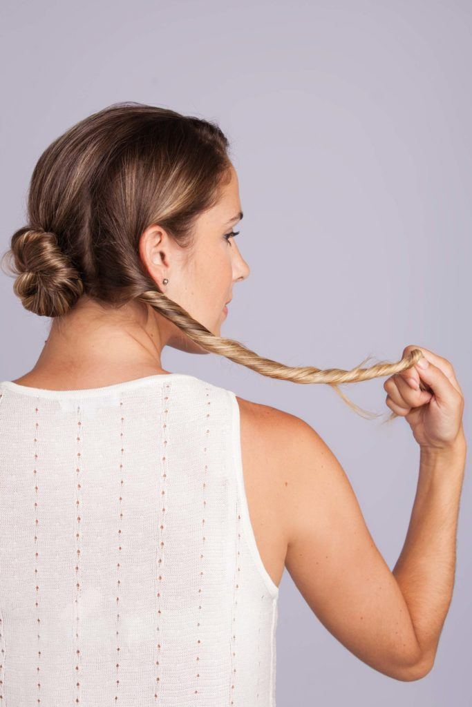 Wedding Hair Buns - Step 4 - woman with bronde hair twisting one section of hair - side view