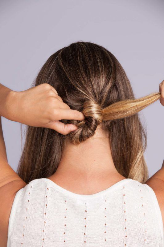 Wedding Hair Buns - Step 5 - woman with bronde hair creating a low bun with twisted hair