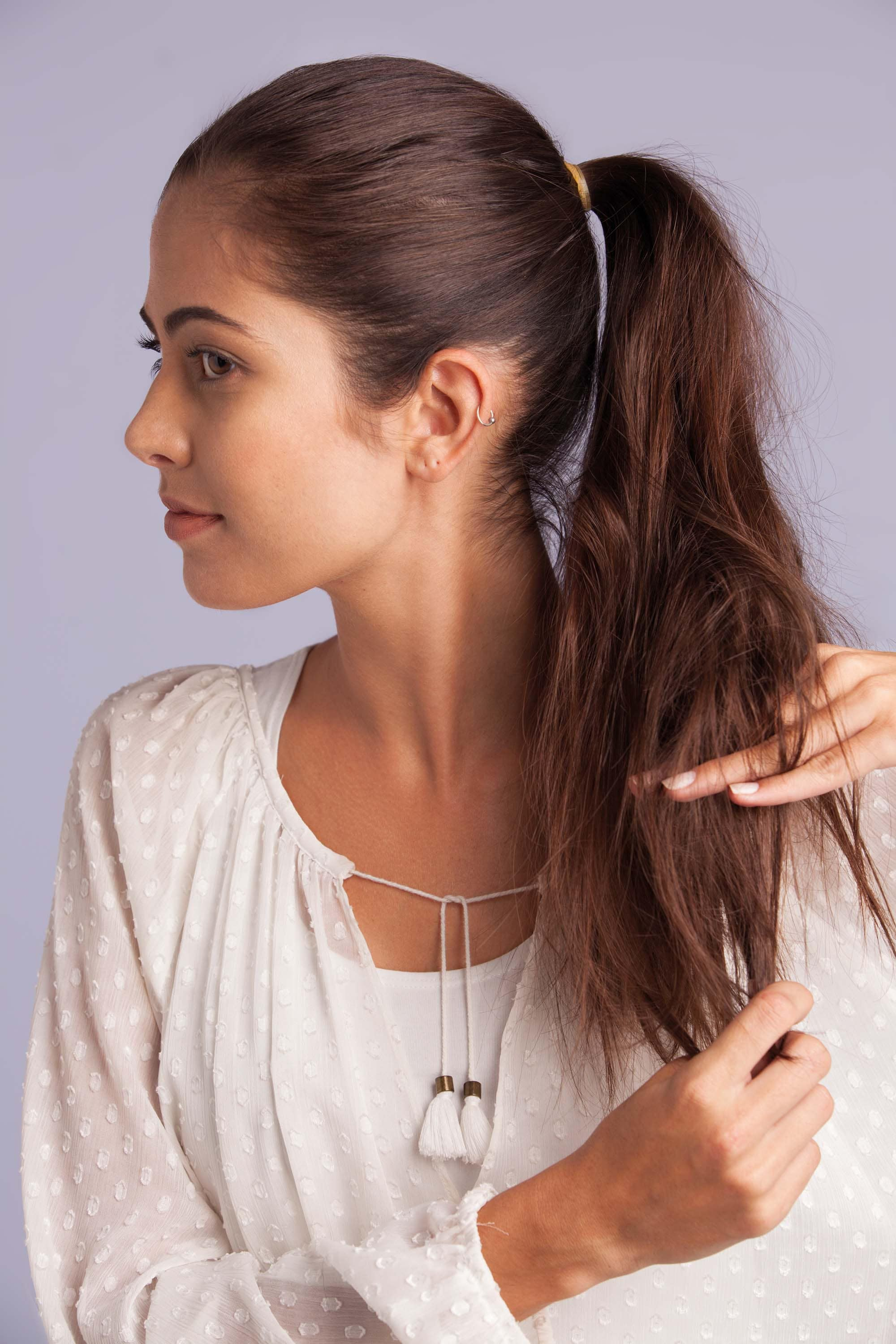 a woman combing her brunette ponytail hair with her hands wearing white clothes