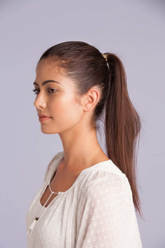 a brunette woman with ponytail hairstyle side view