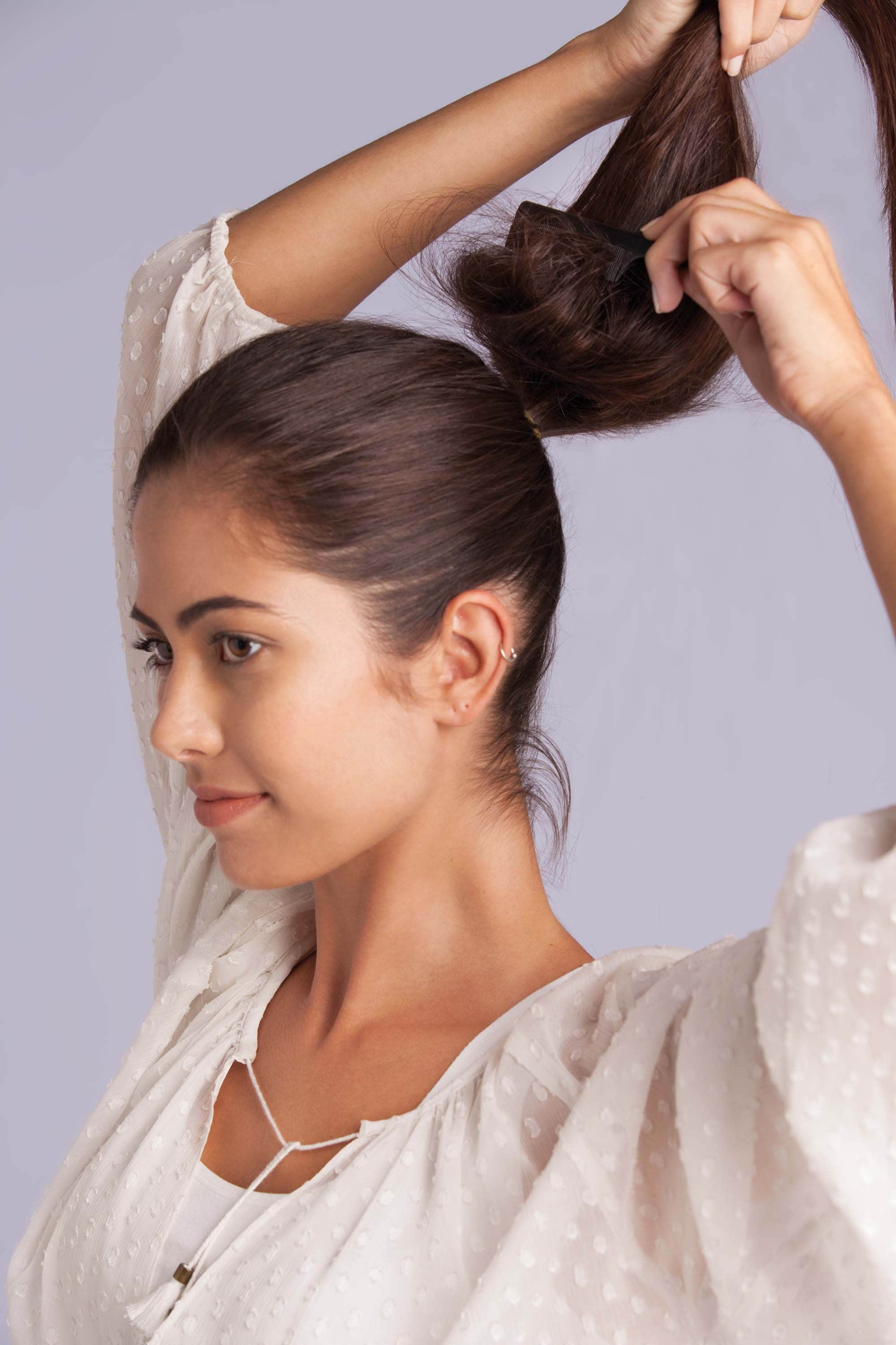 a woman combing her ponytail to make volume