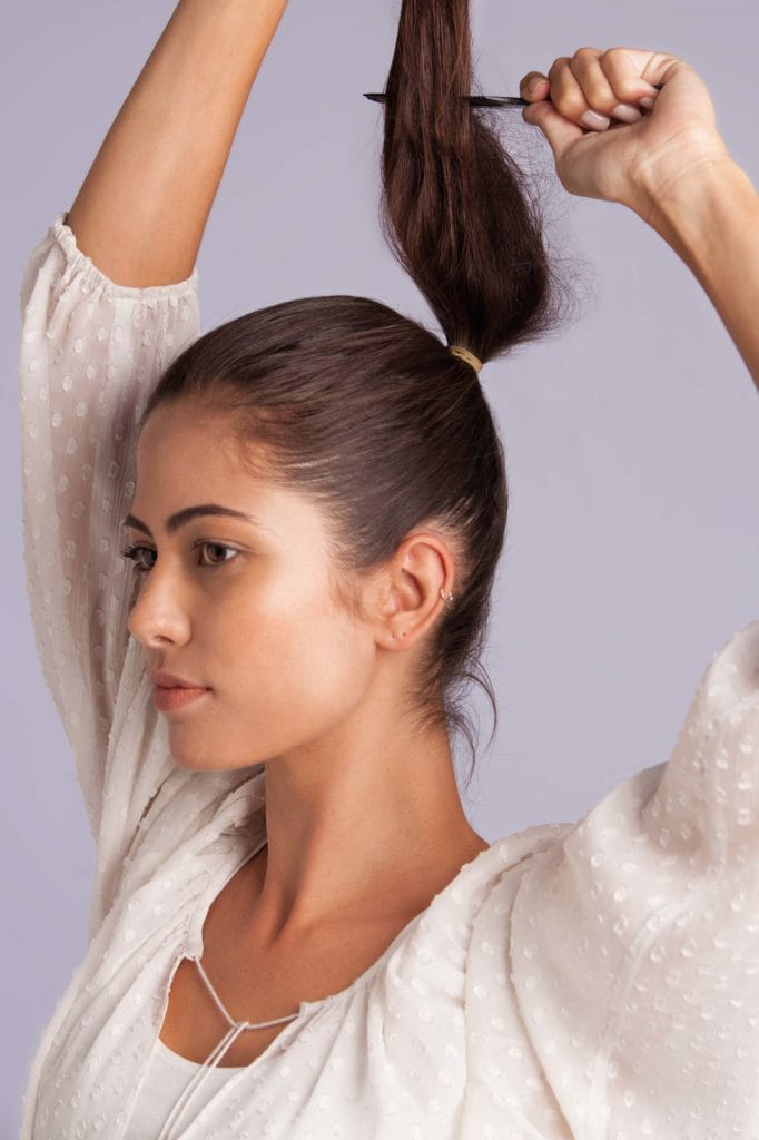 a girl adds volume to ponytail lift hair up and tease