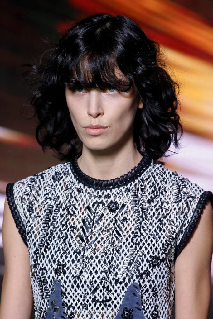 hairstyles for square faces: a model with wavy black long hair looking straight