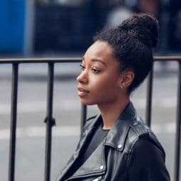 an afro woman with simple hairstyles messy curly bun wearing leather jacket on a street