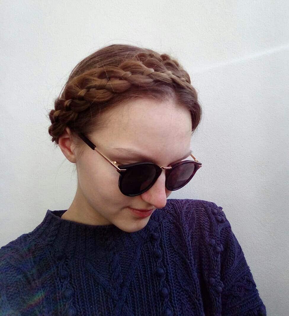 a woman with milkmaid braid on her brown hair smiling while wearing a sunglasses