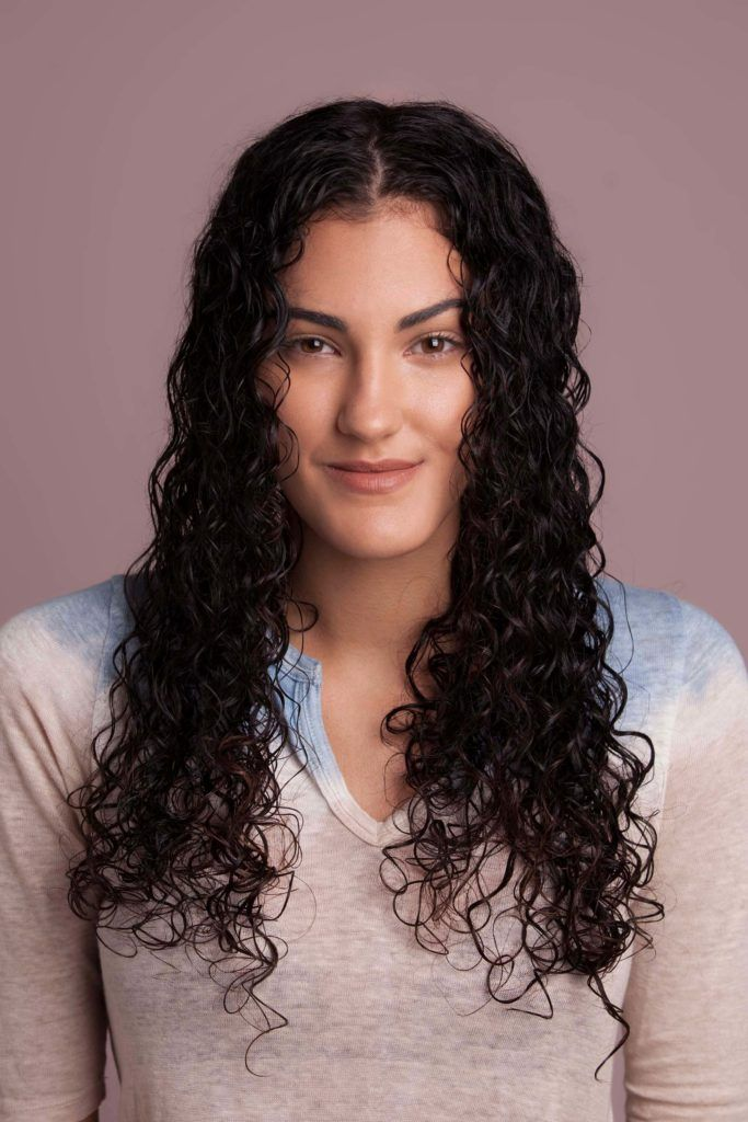 brunette woman styles long curly hair and lets hair dry