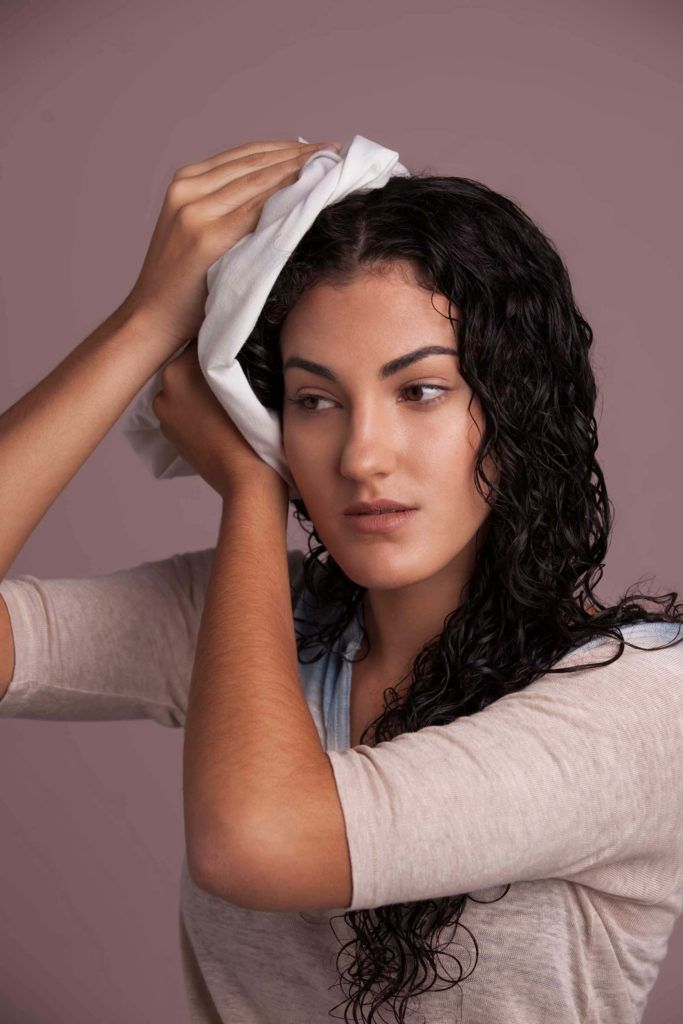 a long curly hair woman drying up her hair using a towel