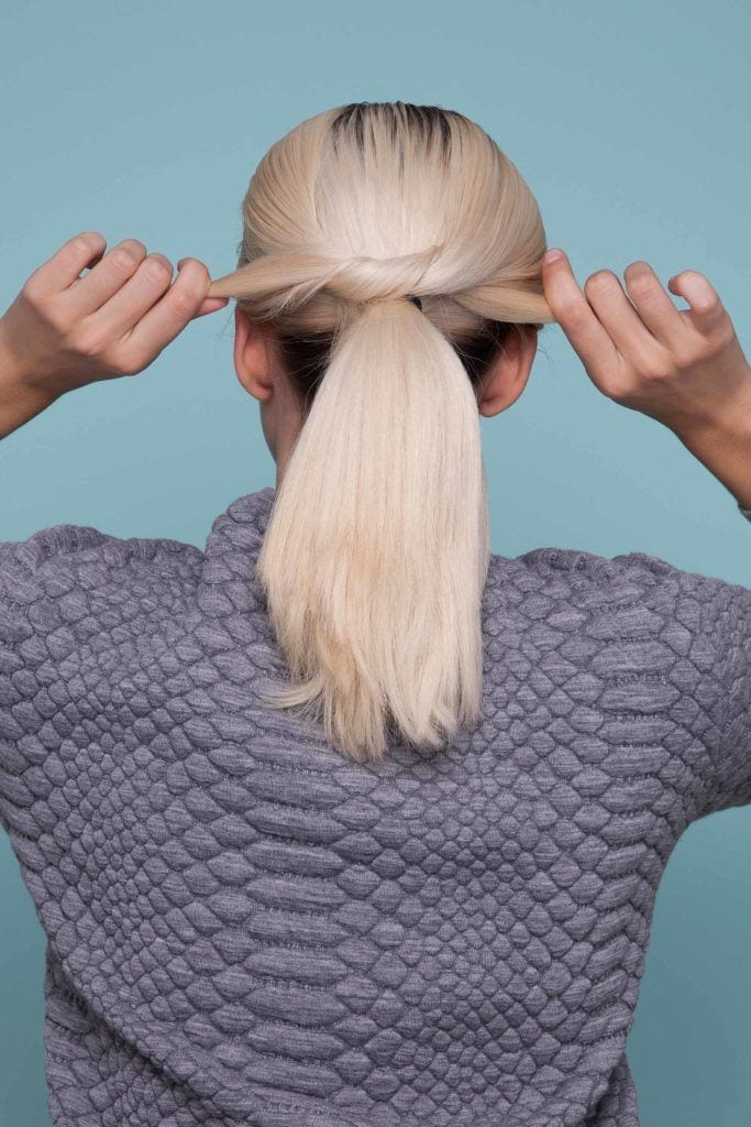 blonde woman creates single knot ponytail and ties a knot