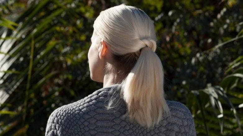 a rear view of a blond woman with ponytail hairstyle standing outside
