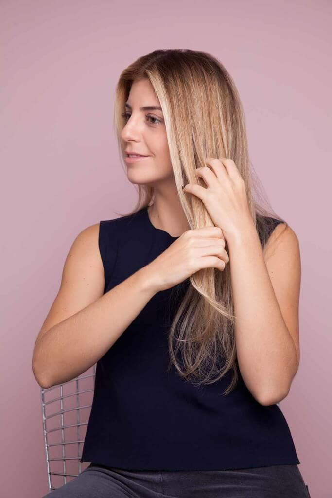 blonde woman creates split crown braid and combs product