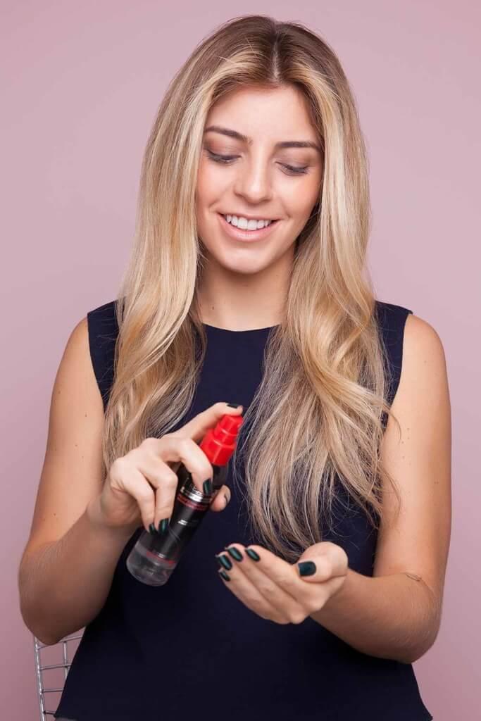 blonde woman creates split crown braid and sprays sea salt spray