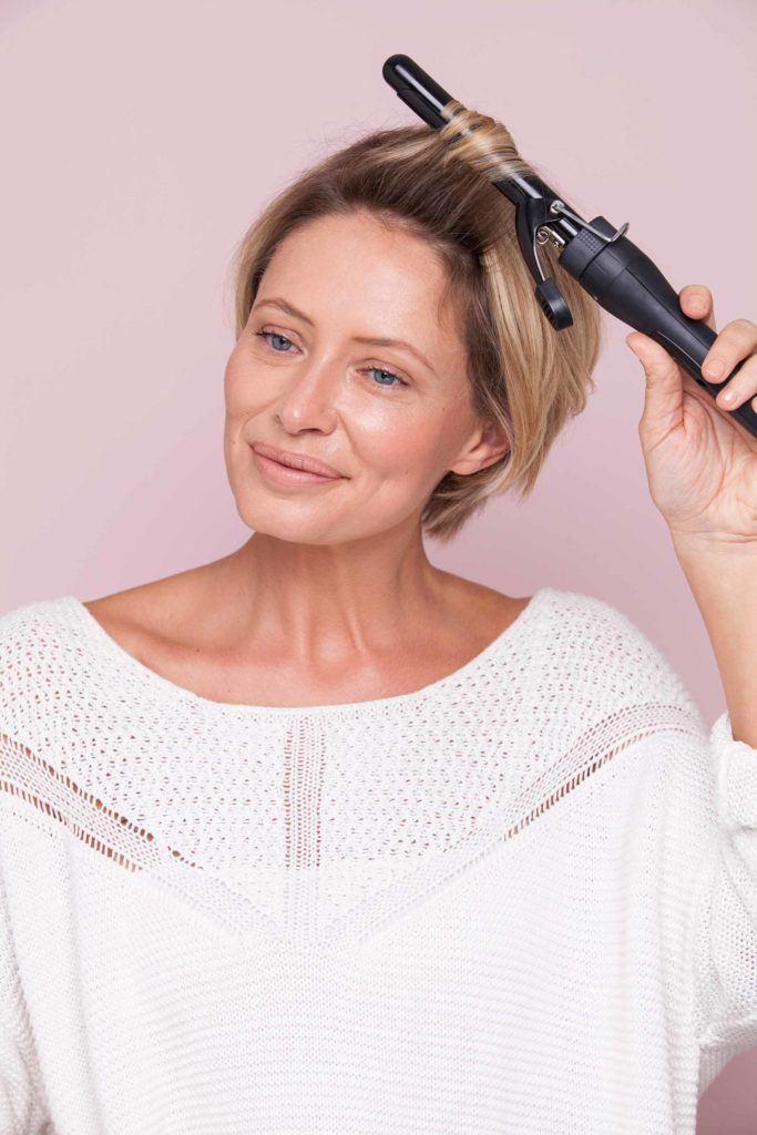 une photo d'une femme frisant ses cheveux courts blonds