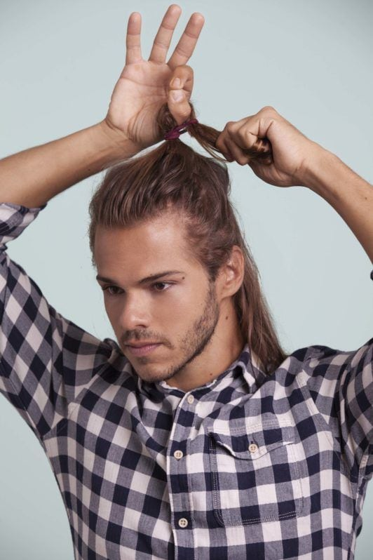 blonde man shows how to make a man bun and twists ponytail