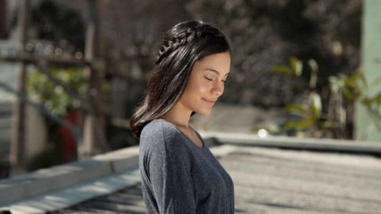 brunette woman creates mid-crown braid and wears it outside