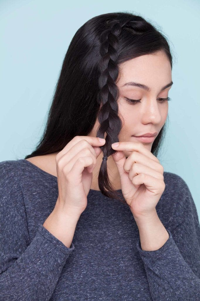 brunette woman creates mid-crown braid and secures braids