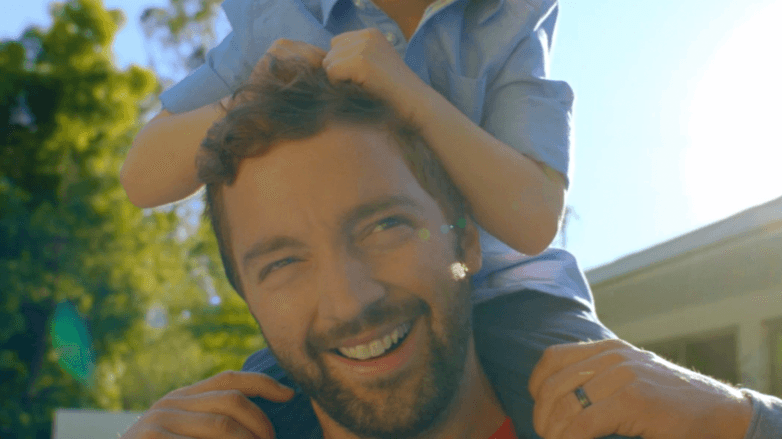 a bearded man standing outside playing with a kid