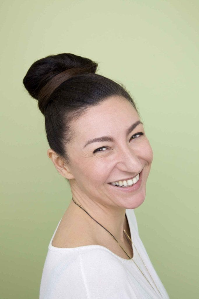 a woman with top knot hairstyle smiling to the camera