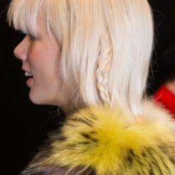 a rear view of a woman with blonde hair wearing a fur coat