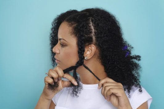 woman braiding hair to the ends to create a natural braided hairstyle