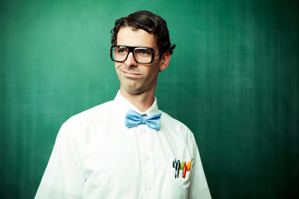 a curly man wearing big glasees and white shirt with butterfly tie