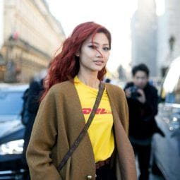 an asian woman with red wavy hair wearing a coat walking on a street