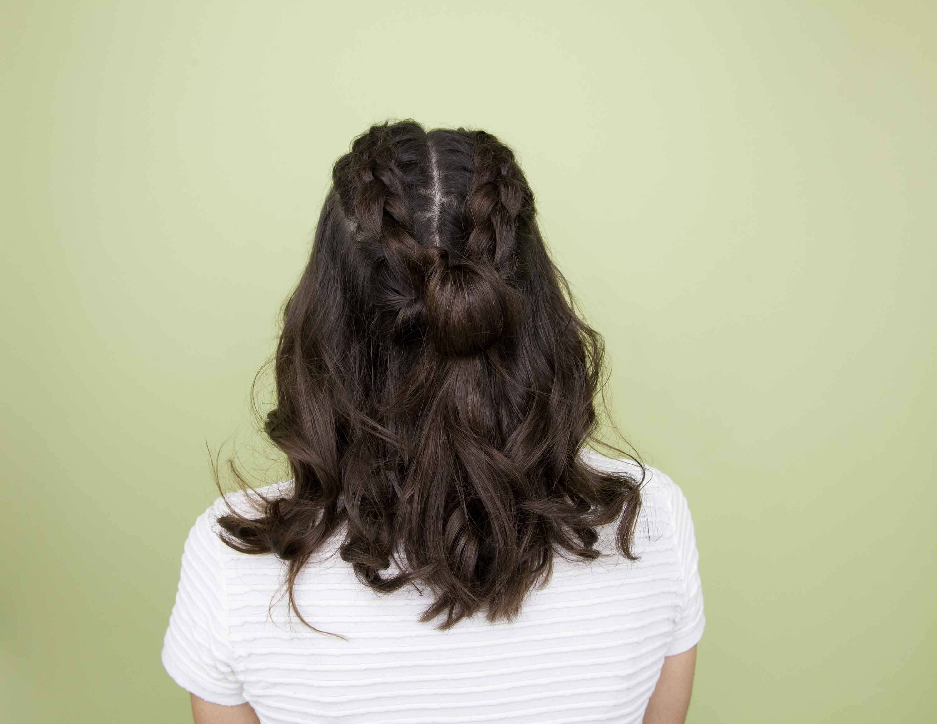 woman showing back view of double braids hairstyle on wavy hair