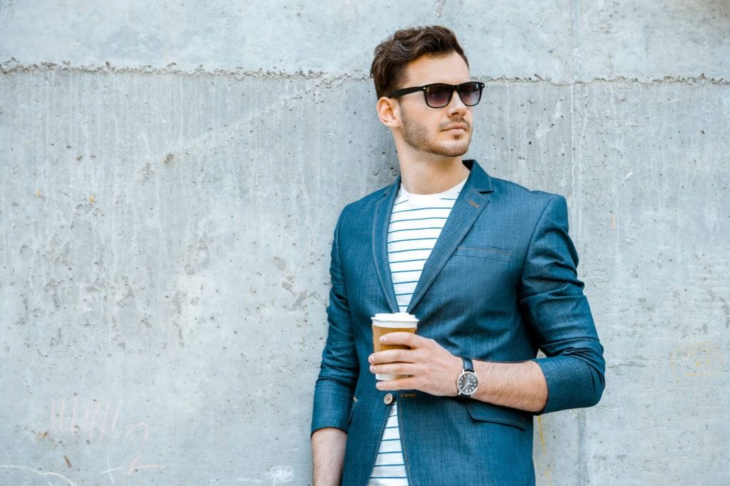 a wavy man standing outside wearing sunglasses and blue suit standing outside while holding a cup of coffee