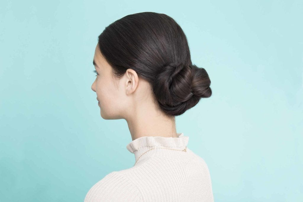 woman posing with pretzel bun hairstyle back view