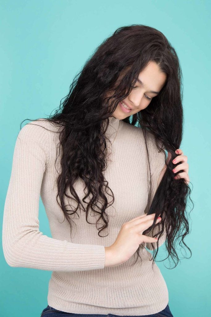 woman with long black hair finger combing and applying hair product