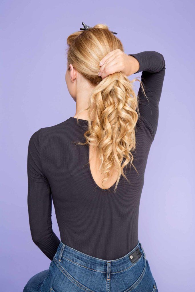 woman with blonde hair creating ponytail with curls