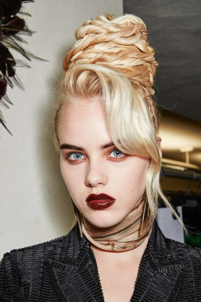 a picture of a woman with dreadlock beehive with bangs blonde hair putting on stron red lipstick