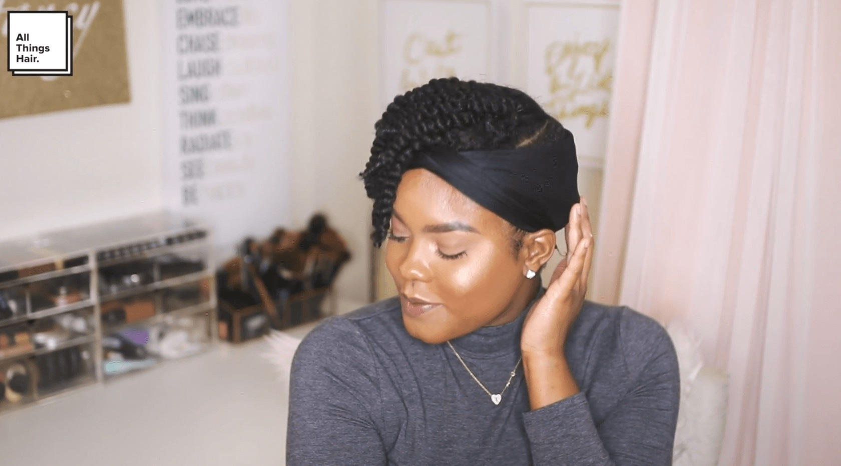 a black woman with braided hairstyle wearing a head scarf touching her hair